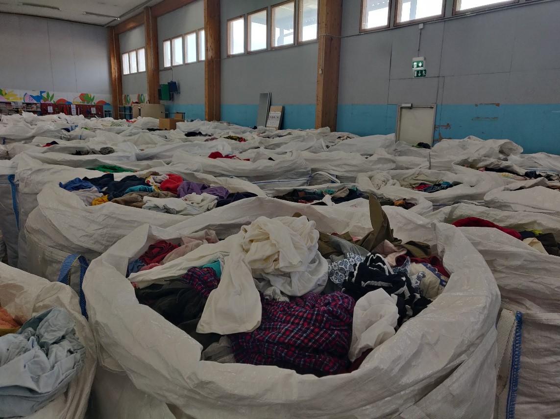 Valkoisia säkkejä, jotka ovat täynnä tekstiilejä.